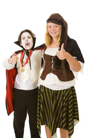 Brother and sister dressed in their halloween costumes, both giving thumbs up sign.   photo