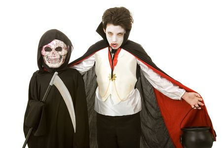 skeleton costume: Two boys dressed for Halloween as a vampire and the grim reaper.  Isolated on white.