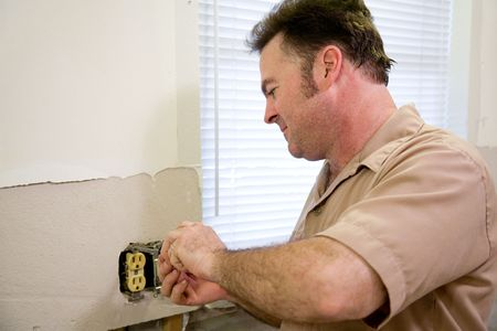 receptacle: Electrician repairing an electrical outlet.  Horizontal with room for text.  Model is a licensed Master Electrician and all work is being performed according to industry code and safety standards.   Stock Photo