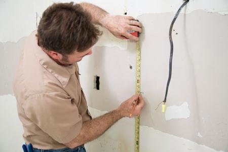 Contratista de medición y marcado el muro seco donde se quiere cortar a cabo una apertura de una caja eléctrica. Auténtico y precisa descripción de contenidos.  Foto de archivo - 3451643