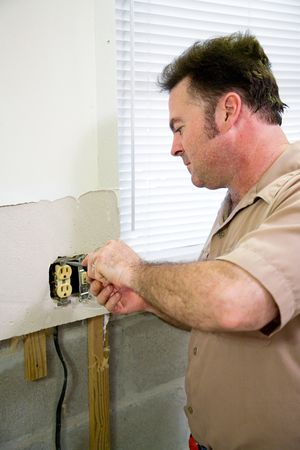 Electrician replacing an old receptacle during a kitchen remodeling job.  Model is a licensed Master Electrician  - all work being performed according to industry code and safety standards. Stock Photo - 3454787
