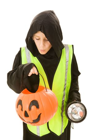 trick or treating: Adorable little boy on halloween with a reflective vest and flashlight for safe trick or treating.  Isolated on white.