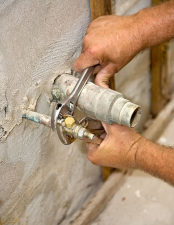 depiction: Closeup of plumbers hands tightening a water pipe.  Authentic and accurate content depiction.
