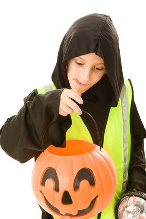 Adorable little boy in his halloween costume with flashlight and reflective vest, eyes the candy in his pumpkin bucket.  Isolated on white.   photo