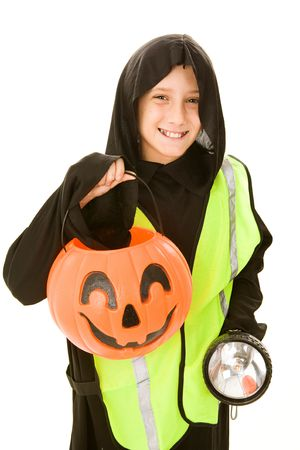 reflective vest: Adorable little boy in his Halloween costume, with a reflective vest and flashlight.