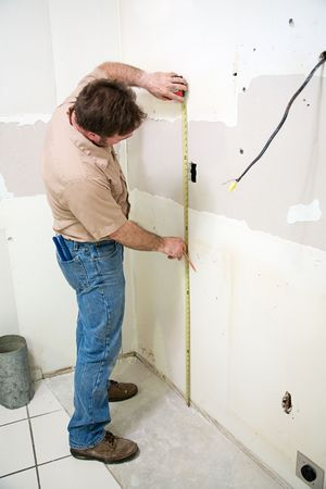 Construction worker measuring the wall during a kitchen remodeling job.  Authentic and accurate content depiction.   Stock Photo