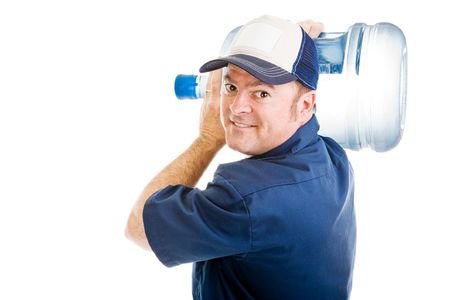 gallon: Friendly delivery man carrying a five gallon jug of drinking water over his shoulder.  Isolated on white.