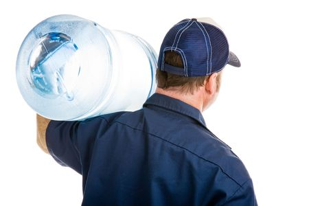 Rear view of a delivery man with a five gallon jug of drinking water over his shoulder.  Isolated on white.