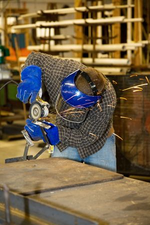Welder using a grinder to smooth a piece of metal.  Authentic and accurate content depiction in compliance with industry code and safety standards.   photo