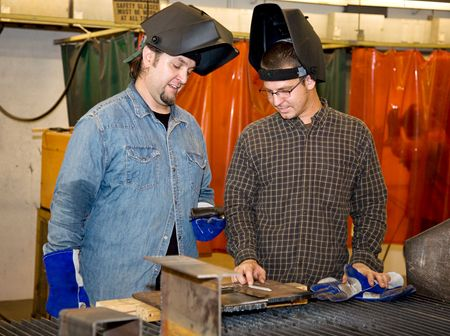 Two welders in a factory discussing how to work a piece of metal.  Authentic and accurate content depiction with all work being performed in accordance with industry code and safety regulations.   photo