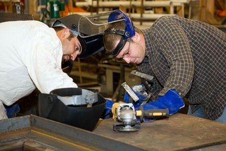 Two welders working together on a difficult metal work project.  Authentic and accurate content depiction in compliance with industry code and safety standards.   Reklamní fotografie