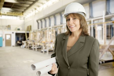 engineering clipboard: Attractive female engineer with blueprints on the floor of a factory.   Stock Photo
