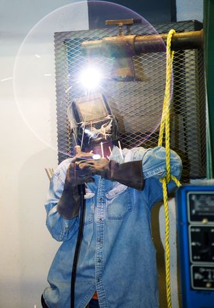 Soldador soldando una pieza de metal sobre la cabeza. El resplandor circular de la lente es una bengala intencional parte de la composici�n. (dise�o en la soldadores casco fue pintado por �l, no marca o logotipo)  Foto de archivo - 3487059