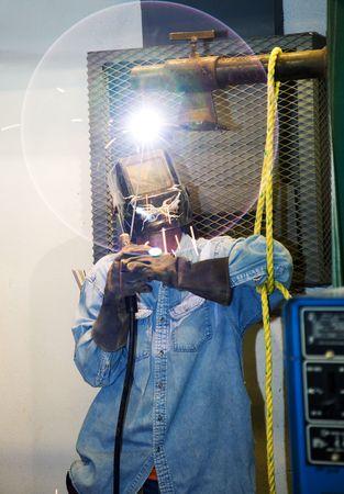 Soldador soldando una pieza de metal sobre la cabeza. El resplandor circular de la lente es una bengala intencional parte de la composición. (diseño en la soldadores casco fue pintado por él, no marca o logotipo)  Foto de archivo - 3487059