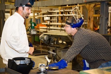 depiction: A machinist in a factory listens as his supervisor critiques metal working project.  Authentic and accurate content depiction in accordance with industry code and safety regulations.