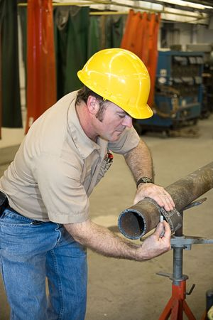 accordance: Metal worker using a flexible ruler to measure pipe and mark it for cutting.  Authentic and accurate content depiction in accordance with industry code and safety standards.