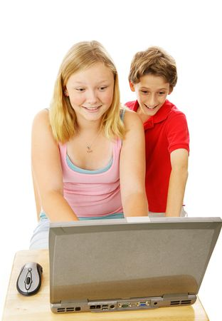 Adorable little boy looks over his teen sisters shoulder as she uses the computer.  Isolated on white.   photo