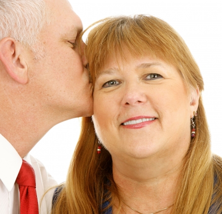 Closeup of a beautiful plus sized woman getting a kiss from a handsome guy.  White background. photo