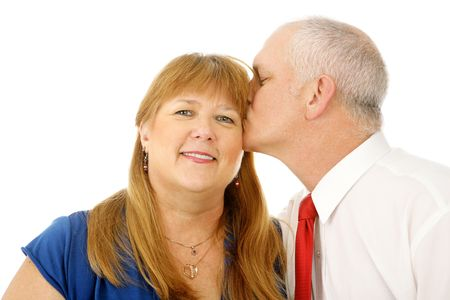 Beautiful mature woman receiving a kiss on the cheek from her husband.  Isolated on white.   photo