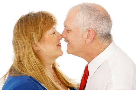 rubbing noses: Adorable mature couple in love rubbing noses with each other. Closeup isolated on white.   Stock Photo