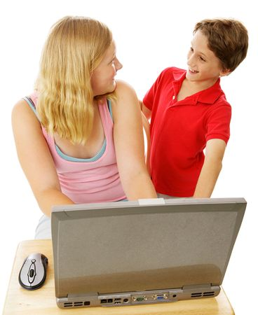 Teen girl using computer and talking with her little brother.  Isolated on white.   Standard-Bild