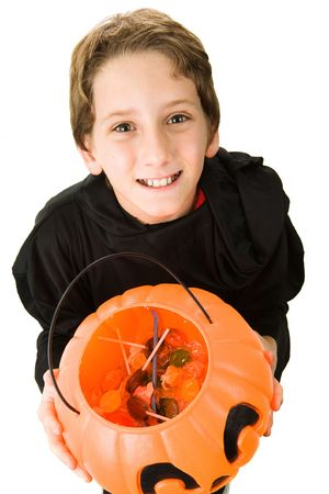 Adorable little boy dressed in his halloween costume and holding out a pumpkin bucket filled with candy.  Isolated on white.   photo