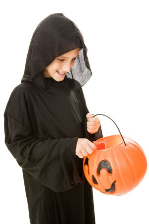 Adorable little boy in his halloween costume, pulling a lollipop from his bucket.  Isolated on white.   photo