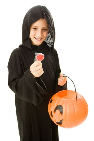 Adorable little trick or treater about to eat a lollipop from his halloween bucket.   Isolated on white. photo