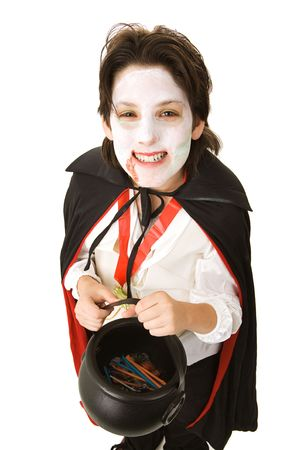 vampire: Cute adolescent boy dressed as a vampire for Halloween and holding a bucket of candy.  Isolated on white.