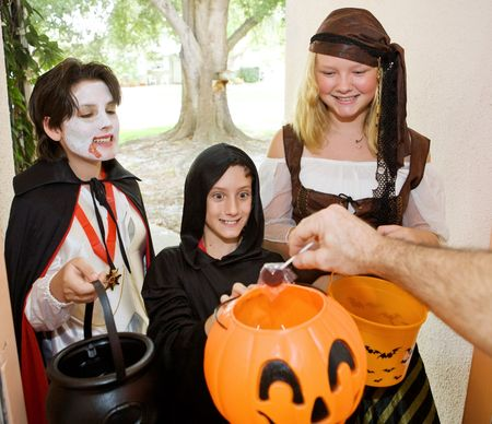 Adorable trick or treaters in the doorway waiting for candy.   Stock Photo
