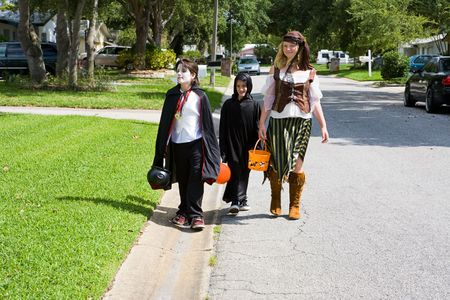 Kids in halloween costumes trick or treating in a suburban neighborhood.
