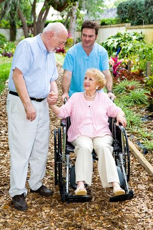 alzheimers: Devoted senior husband visits his wife with alzheimers disease in the nursing home.   Stock Photo