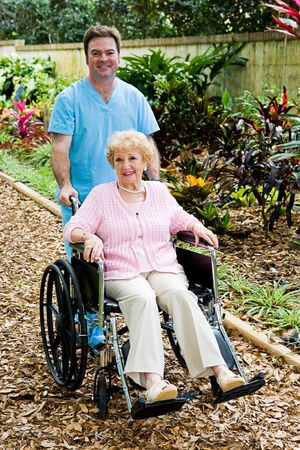 companion: Disabled senior woman in a wheelchair with her male nurse companion.  Stock Photo