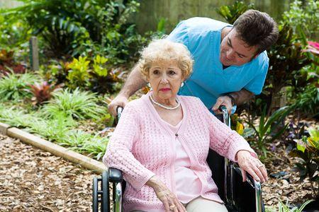 ordelijk: Senior vrouw in verpleeghuis is depressief gevoel en vergeten. Haar geordende probeert te troosten haar.