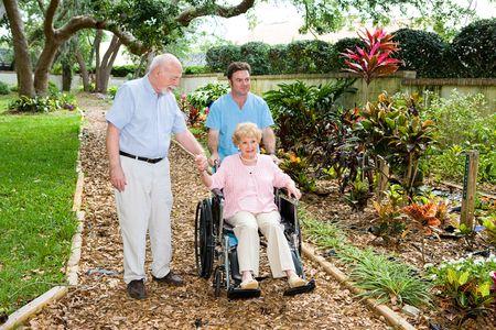 ordelijk: Senior vrouw in een rolstoel wordt gelopen door het verpleeghuis tuin door een ordelijke en haar man.