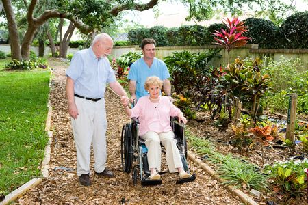 hospice: Senior woman in a wheelchair being walked through the nursing home garden by an orderly and her husband.