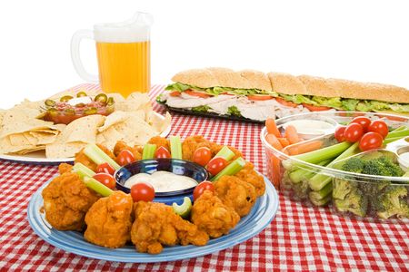 Table set with a variety of party foods and a pitcher of beer.  White background.   photo