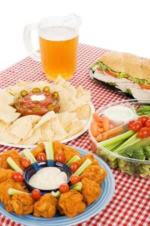 Table set with party snack food platters and a pitcher of beer.  photo