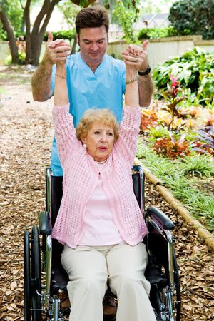 regain: Physical therapist helping a disabled senior woman to regain mobility in her upper limbs.   Stock Photo