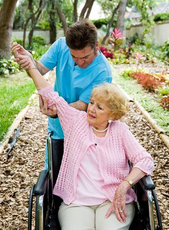 Senior woman with arthritis in her shoulder receives physical therapy in outdoor setting.   photo