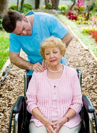 Senior woman in wheelchair receives massage therapy from a physical therapist.