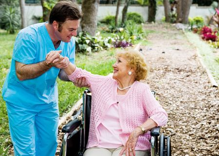 physical therapy: Beautiful disabled senior woman receiving physical therapy in an outdoor setting.