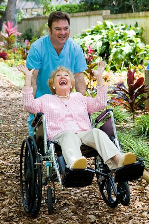 assisted living: Friendly orderly and senior lady having great fun as he pushes her wheelchair.   Stock Photo