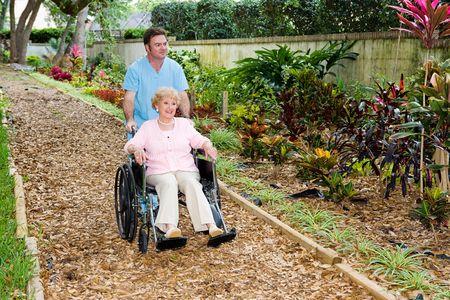 Nursing home orderly pushing a disabled senior woman through the garden.   photo