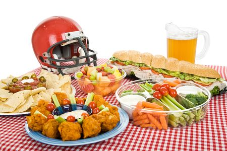 Table set with munchies for a Super Bowl party.  White background.