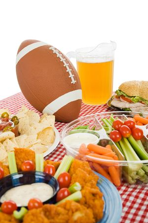 football party: Table set with snack foods for a Super Bowl party.  (focus on football) Vertical view with white background.   Stock Photo