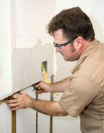 accordance: Electrician installing wiring in an insulated wall.  Focus on electrician.   Authentic and accurate content depiction in accordance with industry code and safety standards.   Stock Photo