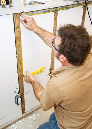 accordance: Electrician installing wiring in an interior wall.   Authentic and accurate content depiction in accordance with industry code and safety standards.
