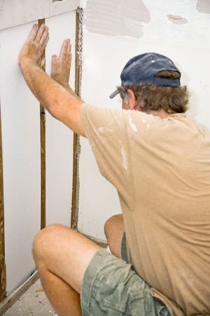 Contractor installing stuff in a section of wall he is replacing.  Authentic and accurate content depiction.   photo