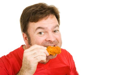 spicy: Middle aged man in football jersey enjoying a tasty fried buffalo wing.  Isolated on white. Stock Photo